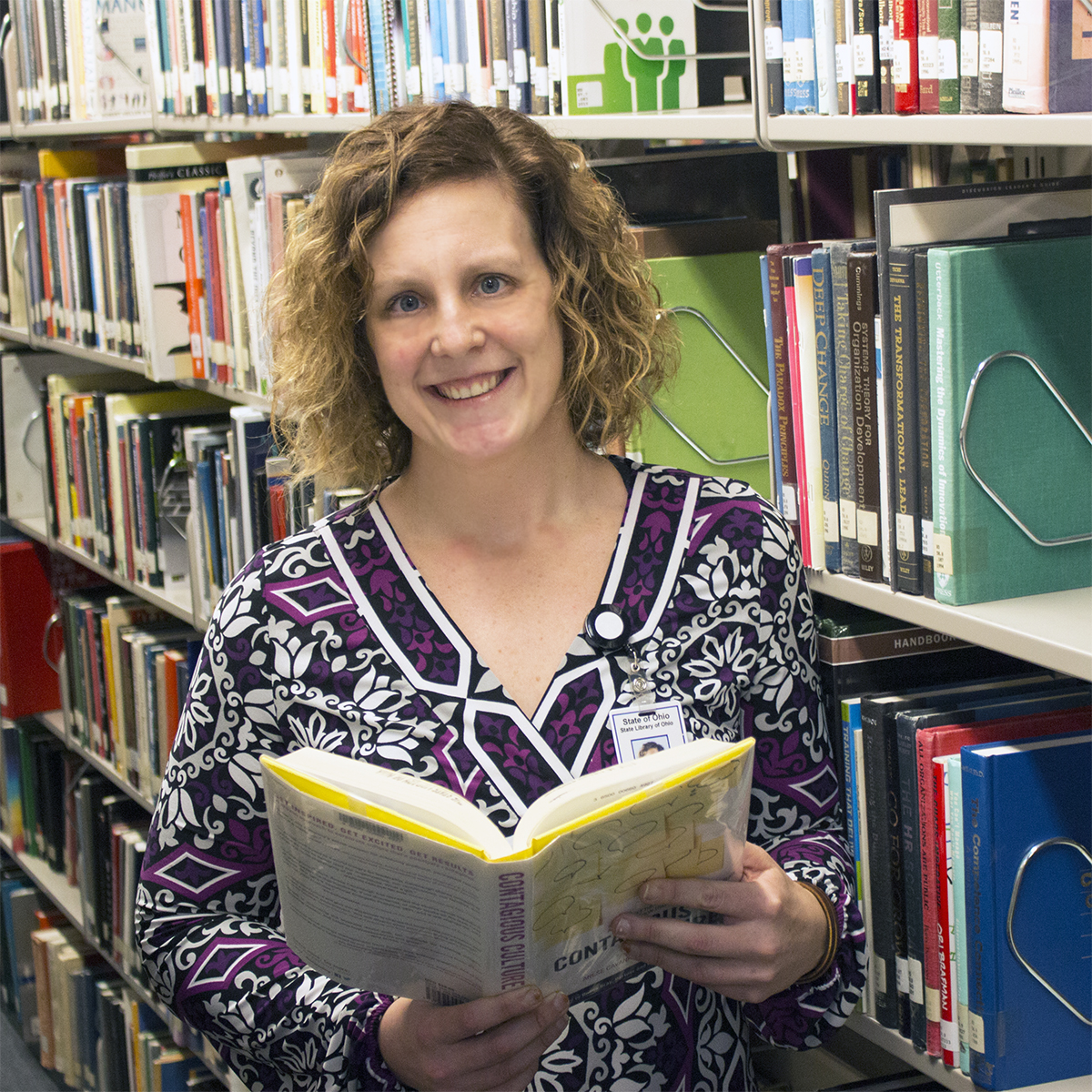 Photograph of Ashleigh Conkey standing in the State Library of Ohio and holding a book.