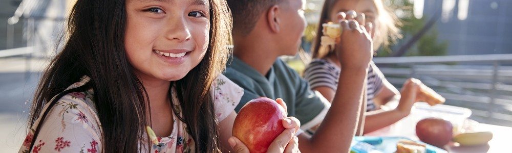Girl at elementary school lunch table smiling to camera - Getty Images
