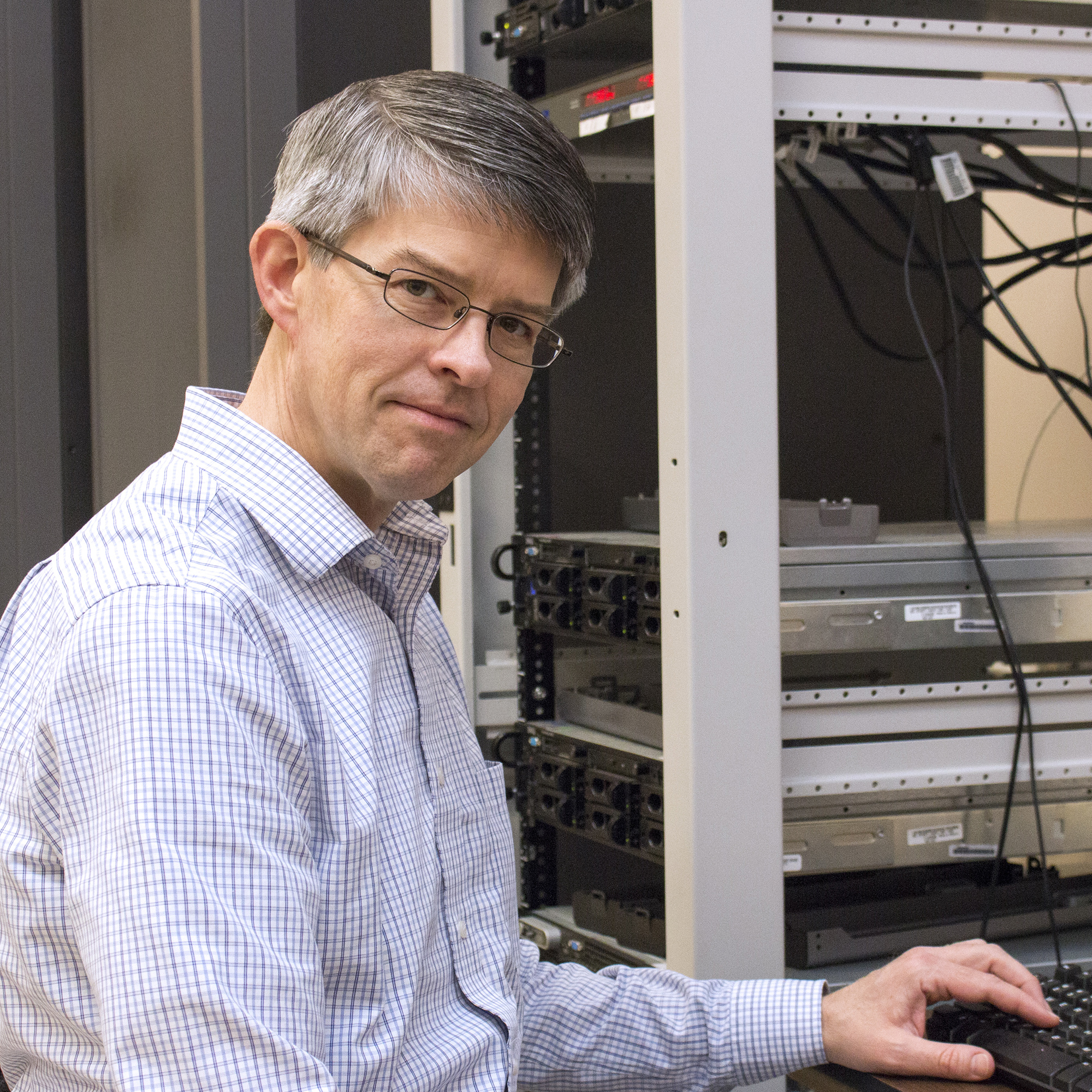 Photo of Peter Kukla sitting in front of keyboard in the server room at the State Library of Ohio